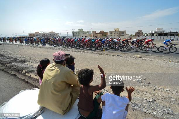 A man with four young children watches a peloton of riders passing by their village during the opening stage a 1765km from Al Sawadi Beach to Naseem...