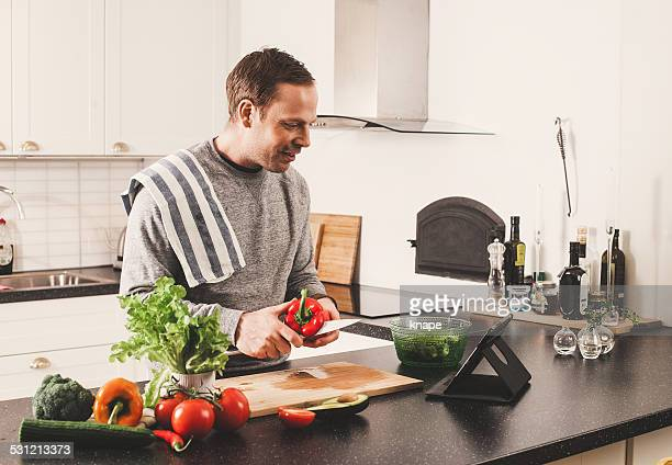 Man with fresh vegetables in kitchen