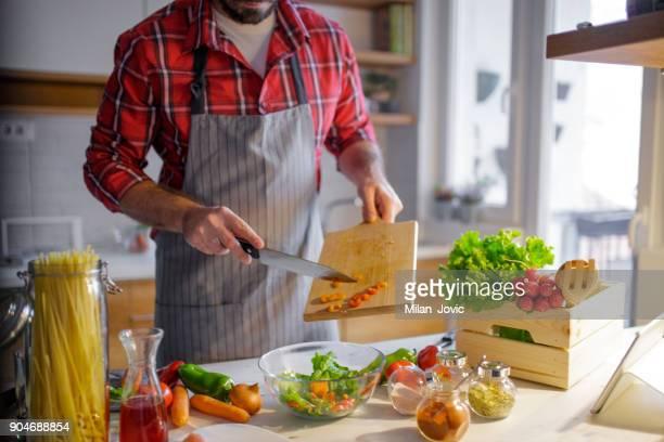 Mann mit frischem Gemüse in der Küche