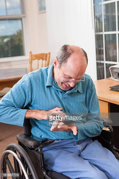 man with friedreich's ataxia in wheelchair using a smartphone with deformed hands - deformed hand stock pictures, royalty-free photos & images