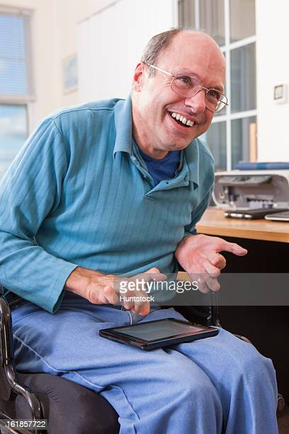 man with friedreich's ataxia in wheelchair using a tablet with deformed hands - deformed hand stock pictures, royalty-free photos & images