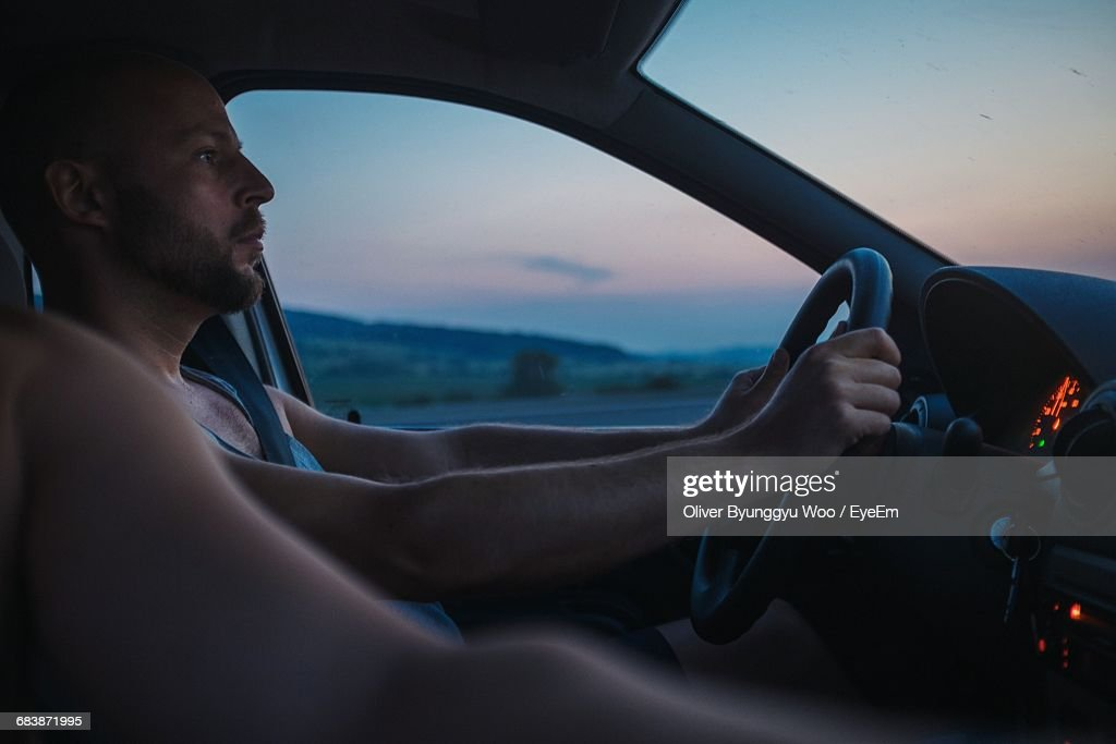 Man With Friend Driving Car During Sunset : Stock Photo