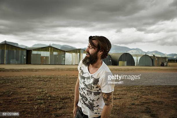 Man with full beard in abandoned landscape