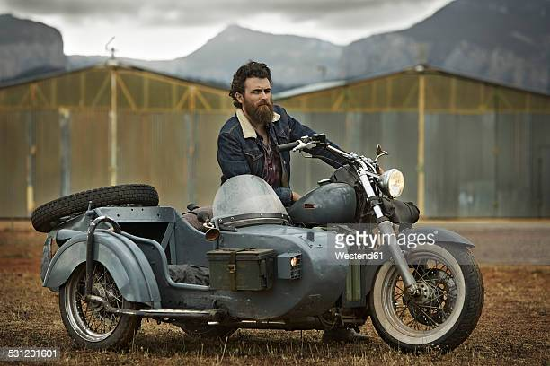 Man with full beard in motorcycle with sidecar