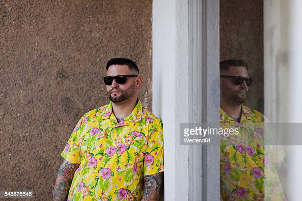Man with fullbeard and tattoos wearing shirt with floral design and sunglasses