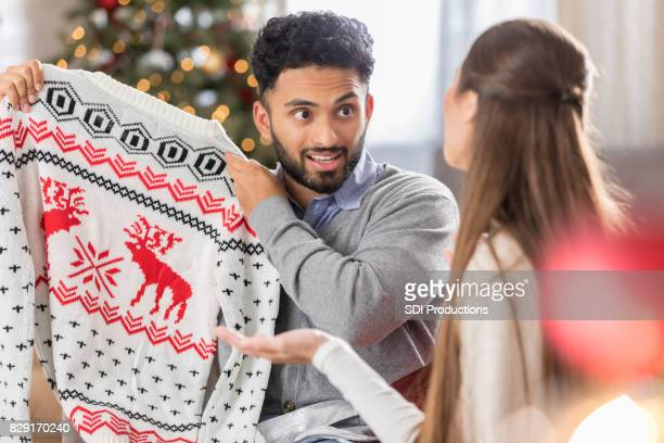 man with funny expression holds up christmas sweater - ugly christmas sweater party stock pictures, royalty-free photos & images