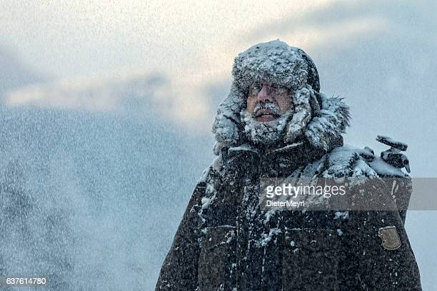man with furry  in snowstorm with cloudy skies and snowflakes - winter weather stock photos and pictures