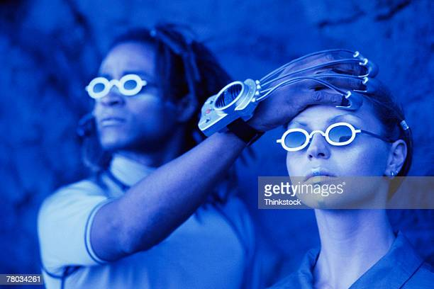 man with futuristic device on hand touching woman's forehead - telepathy stock pictures, royalty-free photos & images