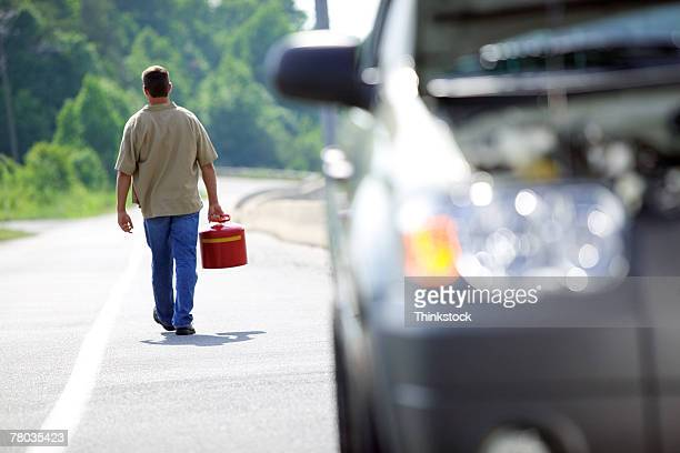 Man with gas can walking away from car