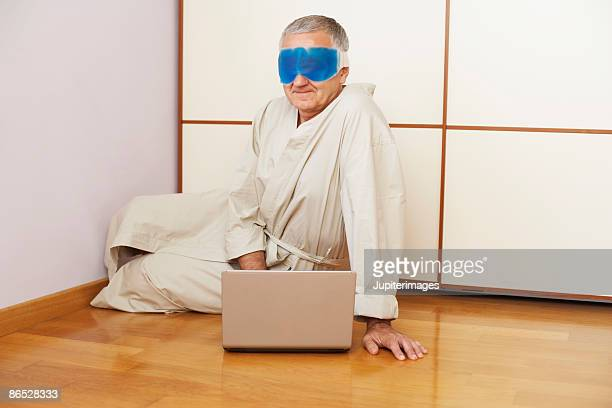 Man with gel mask and laptop computer