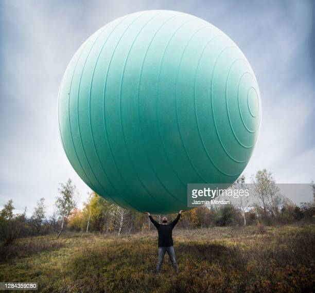 man with giant ball in nature - ball stock pictures, royalty-free photos & images