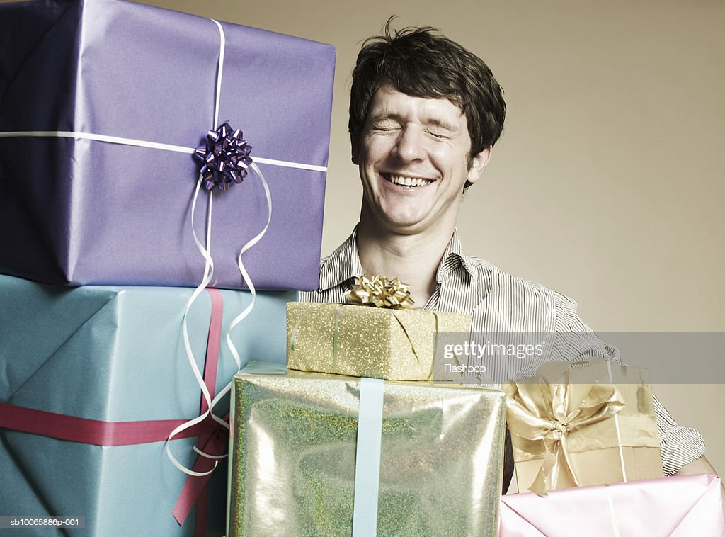 Man with gift boxes, eyes closed, smiling : Stock Photo