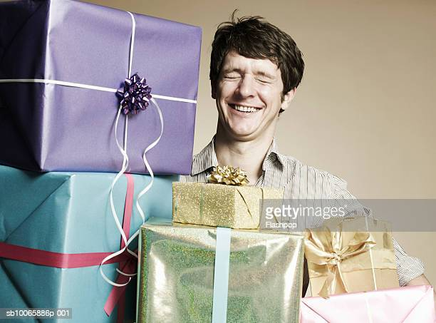 Man with gift boxes, eyes closed, smiling