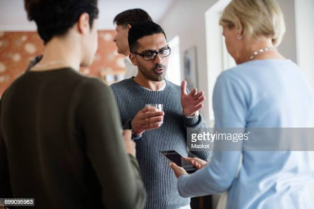 man with glass gesturing while talking to woman holding phone at social gathering - fugitive stock photos and pictures