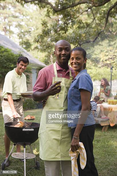 Man with glass of beer and apron standing with woman at cook out