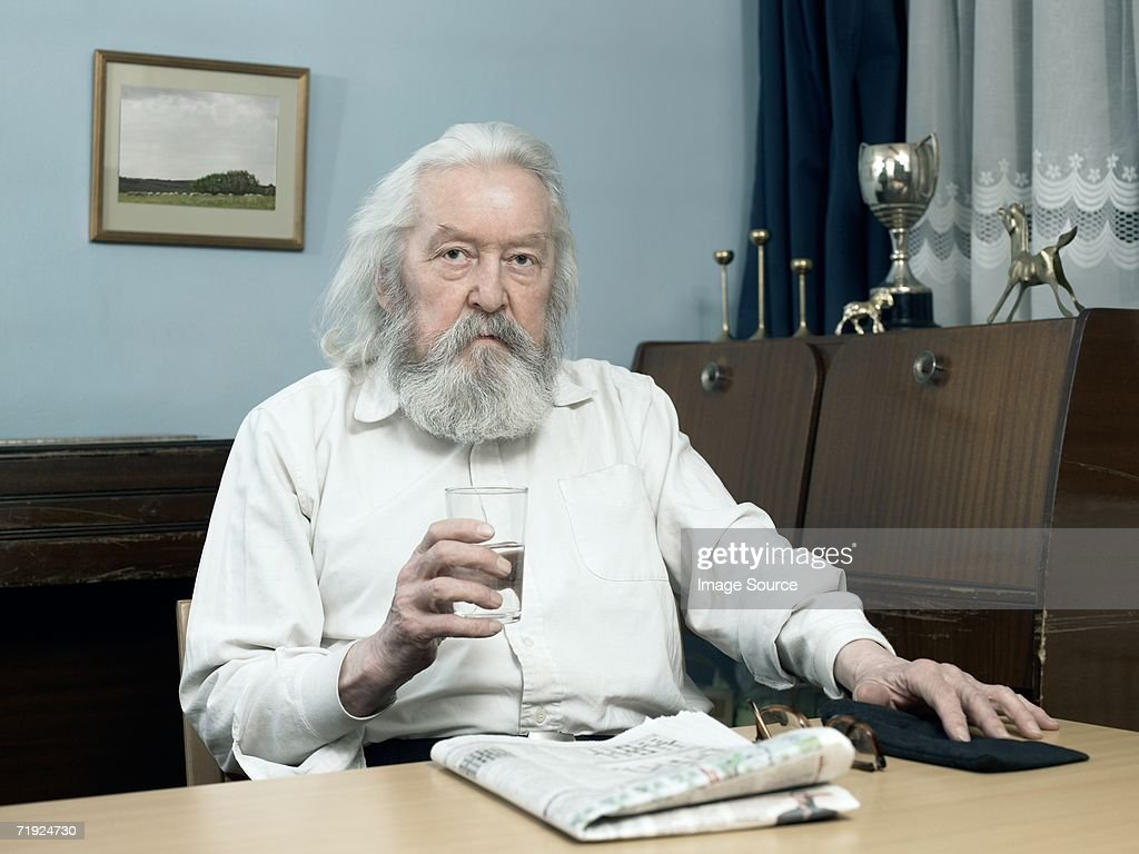 Man with glass of water and newspaper : Stock Photo