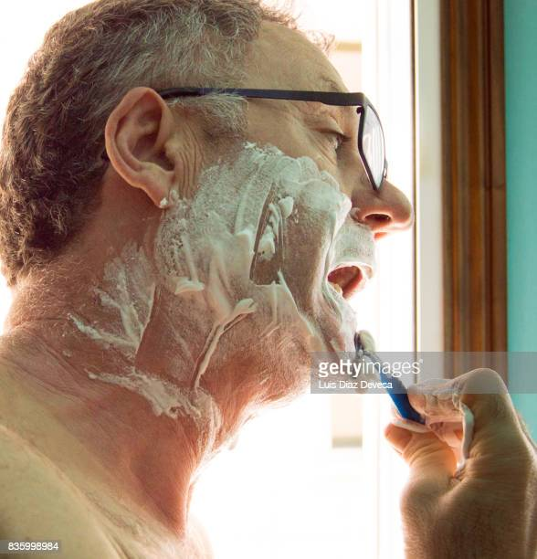 Man with glasses shaves