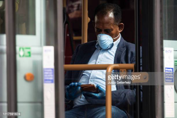 A man with gloves and a mask sits on a bus outside St Thomas' Hospital on April 08 2020 in London England Prime Minister Boris Johnson has spent a...