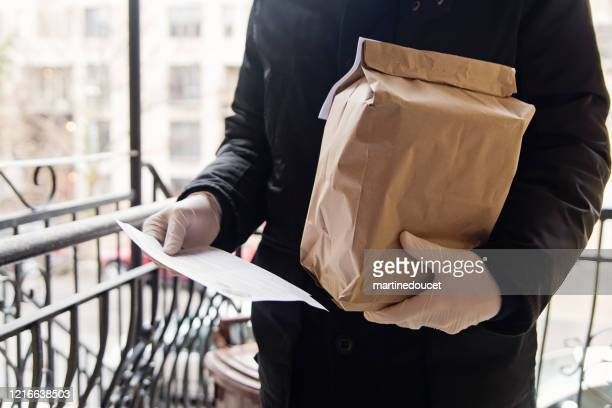 "man with gloves delivering food at the door. - ""martine doucet"" or martinedoucet stock pictures, royalty-free photos & images"