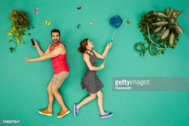 man with gps pointing in one direction, woman is catching butterflies - homem pegando mulher imagens e fotografias de stock