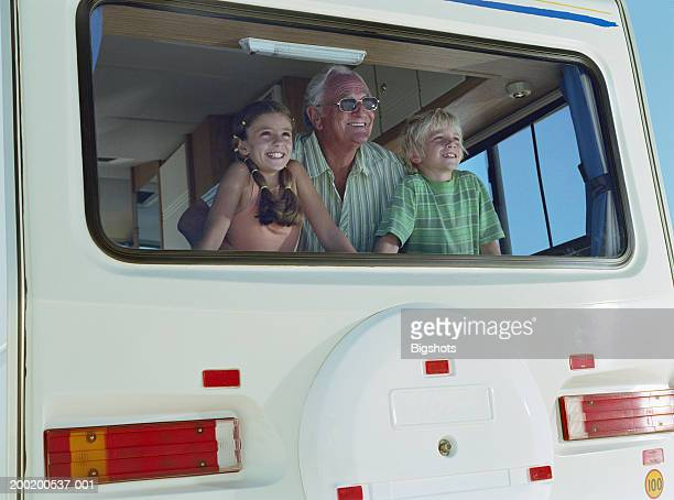 Man with grandchildren (7-10) looking out back window of campervan