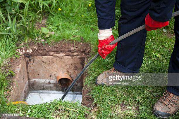 man with ground open unblocking a drain with a tool - sewer stock pictures, royalty-free photos & images