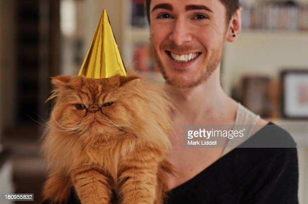 Man with grumpy orange cat wearing a party hat