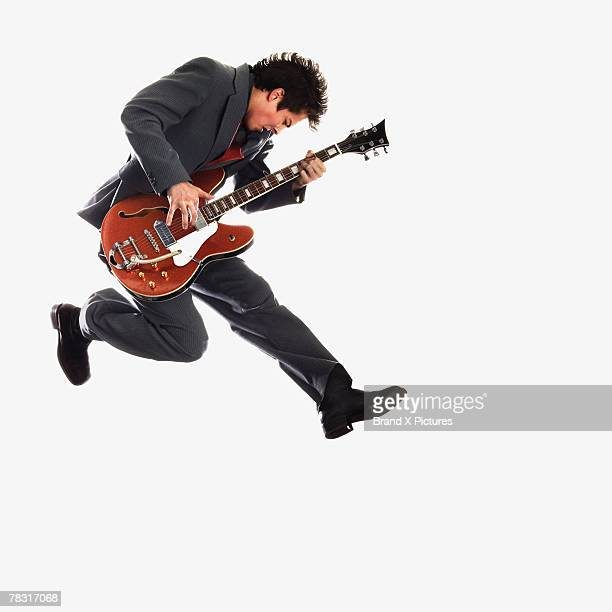Man with guitar jumping