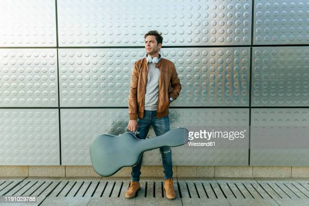 man with guitar standing in front of a silver wall - guitar case stock pictures, royalty-free photos & images