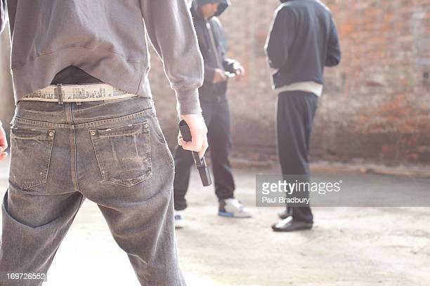 man with gun approaching drug dealers - drug dealer stock pictures, royalty-free photos & images