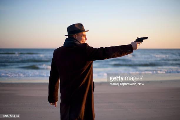 Man with gun on beach.