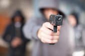 Man with gun pointed at viewer