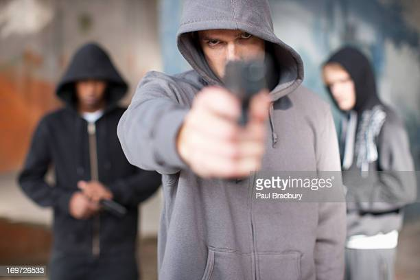 man with gun pointed at viewer - gang stock pictures, royalty-free photos & images