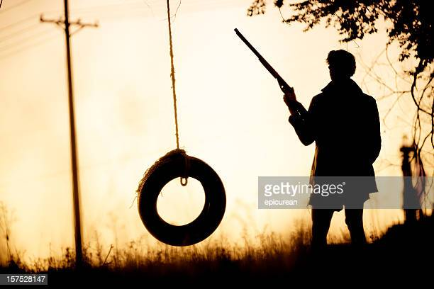Man with gun standing by a tire swing