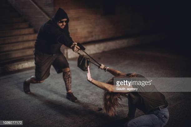 homem com arma roubar bolsa de mulher jovem - roubando crime - fotografias e filmes do acervo