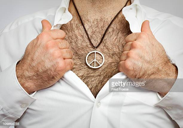 man with hairy chest wearing peace symbol - hairy chest stock-fotos und bilder