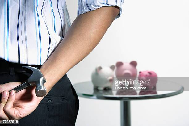 Man with hammer approaching three piggybanks on table