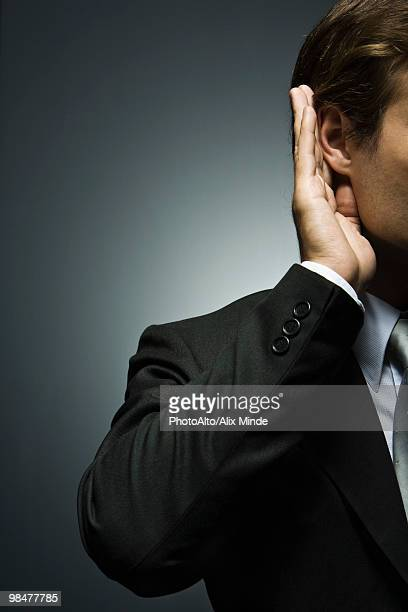 Man with hand cupped around ear listening attentively