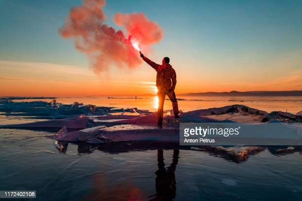 man with hand flare at sunset on ice. baikal in winter - saluting stock pictures, royalty-free photos & images
