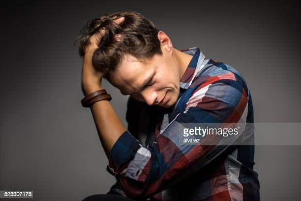 homem com a mão no cabelo contra fundo cinza - mão no cabelo - fotografias e filmes do acervo