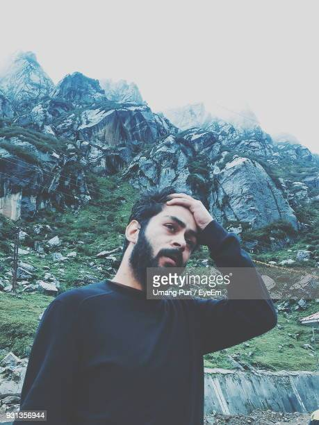 man with hand in hair against mountains - delhi stock pictures, royalty-free photos & images