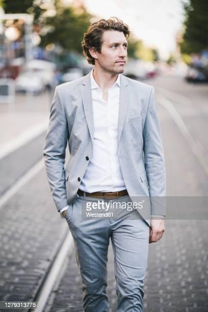 man with hand in pocket walking on tramway in city - elegante kleidung stock-fotos und bilder