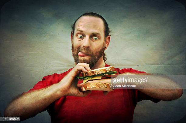 man with hand in sandwich - scott macbride stock pictures, royalty-free photos & images