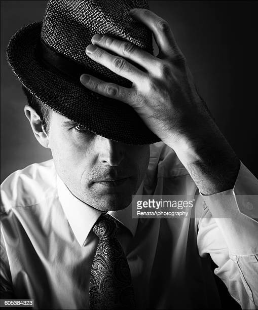 Man with hand on hat