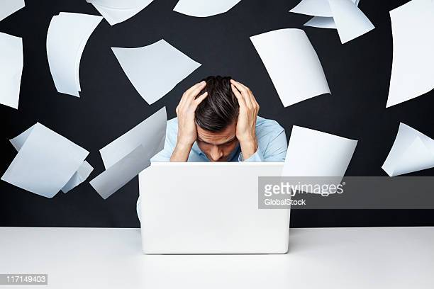 man with hand on head looking at laptop with papers flying - excess stock pictures, royalty-free photos & images