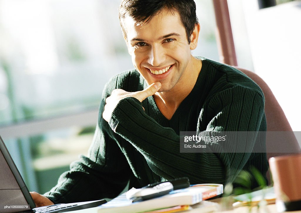 Man with hand on laptop computer, smiling, portrait : Stockfoto