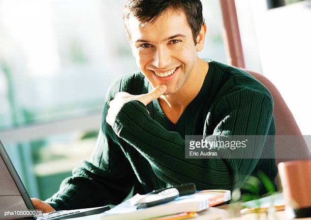 Man with hand on laptop computer, smiling, portrait