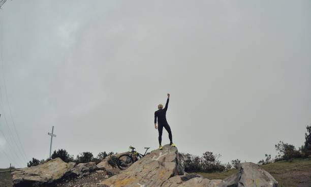 Man With Hand Raised Standing On Rock Against Sky