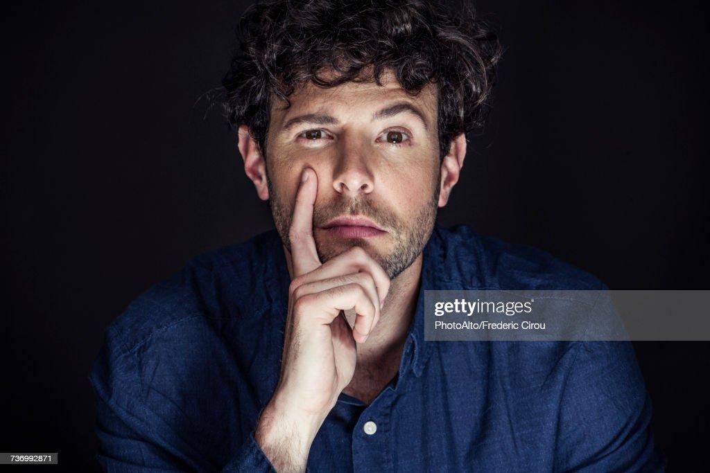 Man with hand under chin, one eyebrow raised : Stock Photo