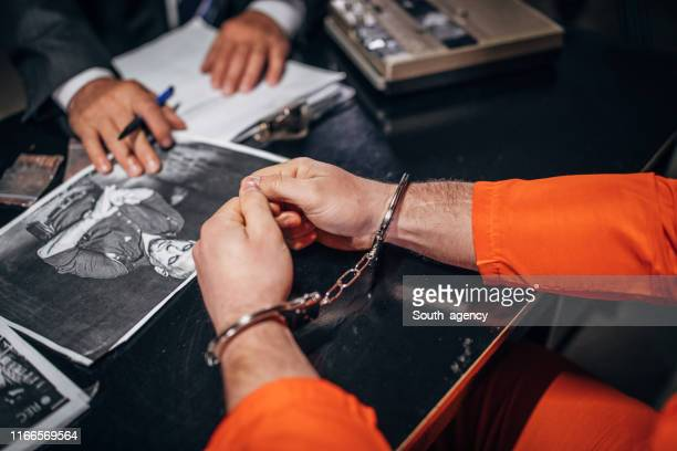 man with handcuffs shaking in interrogation room - legal trial stock pictures, royalty-free photos & images
